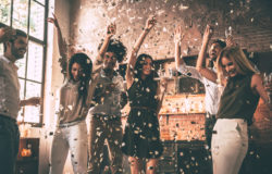 64179434 - enjoying cool party. group of happy young people throwing confetti and jumping while enjoying home party on the kitchen
