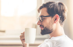 66449949 - handsome man in eyeglasses is smelling the aroma of coffee and smiling while resting at home